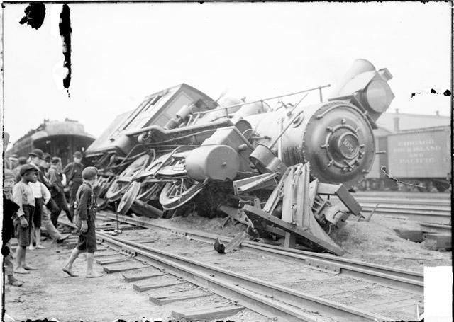 [Boys, including one African American, standing on railroad tracks near a train engine that derailed in the Rock Island Suburban Railroad train accident at 47th street]