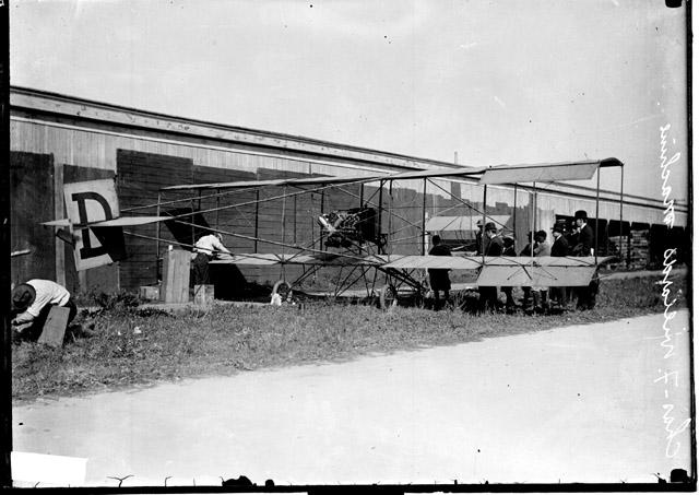 [Charles F. Willard's airplane parked alongside a low building, a group of men standing next to the wing on one side of the plane, a man working on the other wing of the plane]