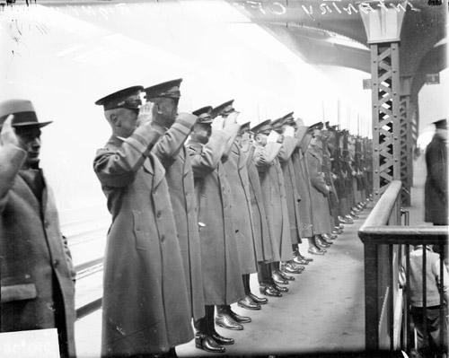 [Infantry officers and soldiers standing on a railroad platform, saluting Secretary of War James W. Good's funeral train]