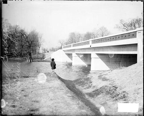 [Child standing on the banks of the Des Plaines River in Des Plaines, Illinois, in front of a new bridge spanning the river]