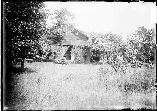 [Back of the Ira Rawn summer residence, seen from across a grassy area]