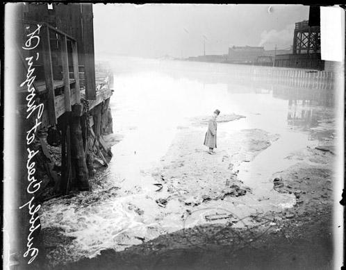 [Bubbly Creek, man standing on crusted sewage]