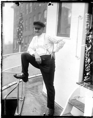[Captain J. W. Petoskey, standing on deck of his rescue steamer on the Chicago River]