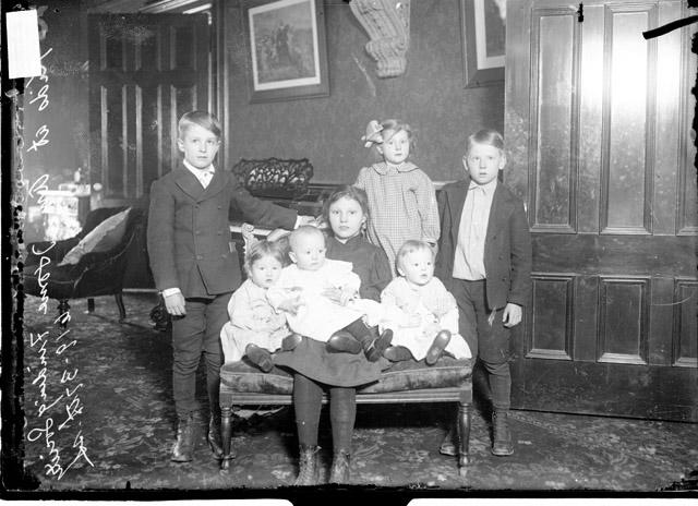 [Seven children sitting on and gathered around a small sofa in a room in the American Home-Finding Society]