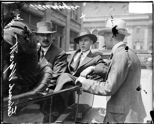 [Bank messenger, Edward Wyatt, sitting in the back of a convertible automobile with an unidentified man]