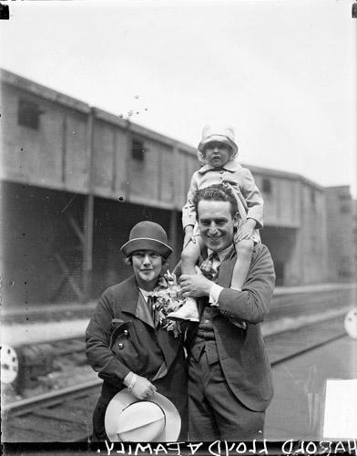 [Actor Harold Lloyd standing with his wife, his young daughter sitting on his shoulders on a railroad platform]