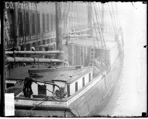 [Bertha Barnes, steamer, docked alongside an industrial building on a waterway in Chicago]