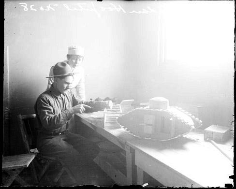 [Fort Sheridan Hospital, wounded soldier making toy tank, nurse watching from behind soldier]