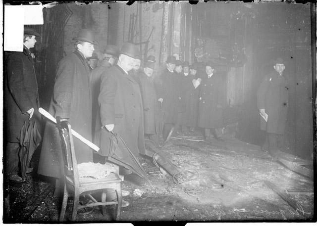 [Coroner Traeger and other men investigating the Iroquois Theater fire, standing among the ruins of the interior of the theater]