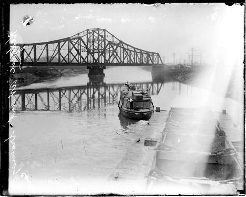 [Barges moving along the drainage canal at South Kedzie Avenue with a railroad spanning the canal in the background]