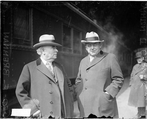 [Anton J. Cermak, President of the Cook County Board of Commissioners, and George E. Brennan, Democratic leader in Chicago, standing next to a train]