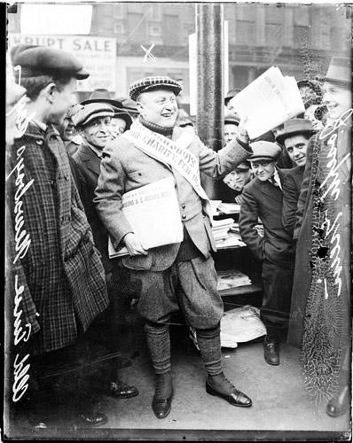 [Joseph Grein holding up newspapers for sale on Old Newsboys Day]