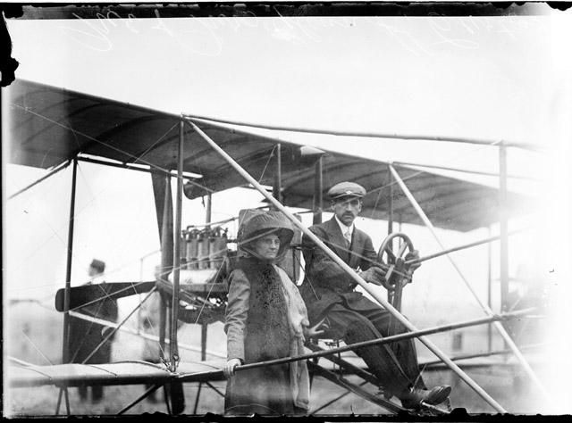 [Glenn Curtiss sitting at the wheel of his biplane, with his wife standing next to him]