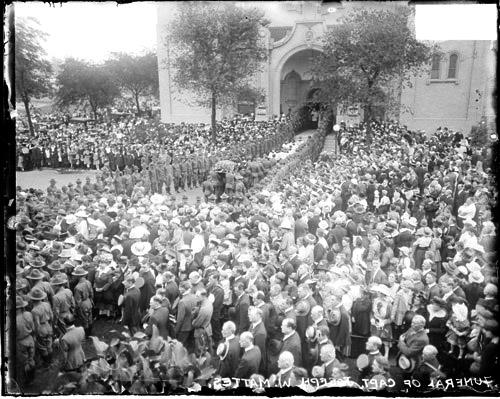 [Crowd standing outside Our Lady of Lourdes Church, for funeral of Captain Mattes, procession heading in to the church]