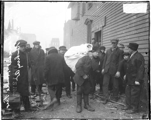[Homeless tenants gathered near a building after their tenement building burned down due to an explosion]