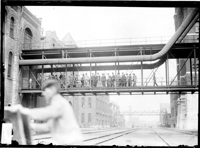 [Chicago Association of Commerce visit to the Pullman Works, showing men wearing suits standing on a raised walkway that connects manufacturing facilities]