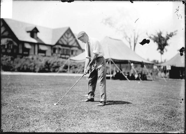 [Golfer, Js. Hollibird, preparing to hit a golf ball on a course near a clubhouse]