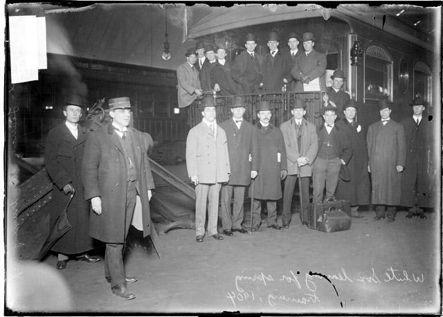 [Baseball team, Chicago White Sox, leaving for spring training, players gathered on railroad platform, train conductor stepping forward]