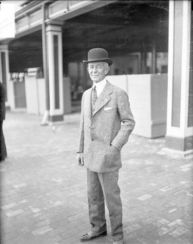 [Horse racing, C. F. Price, standing in front of a building at the Washington Park Race Track]