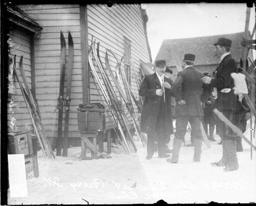 [Group of men standing on snow-covered ground in front of a building at the Norge Ski Club]