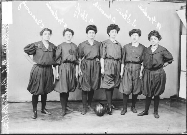 [Hull House girls' basketball players Isacowits, Goodman, Shiff, Horwich, Slein, and Gordon, standing in front of a backdrop]
