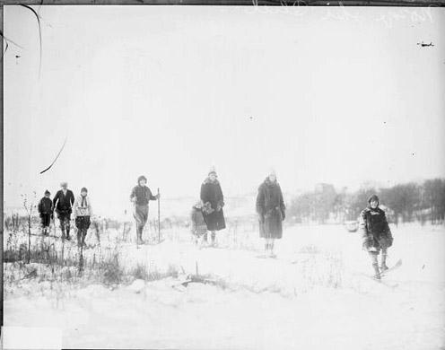 [Group of unidentified adults and children skiing over snow-covered ground at the Norge Ski, dark exposure]