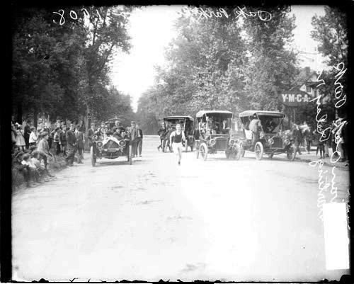 [Athlete K. Sullivan of the Oak Park High School relay team, running past automobiles on a street]