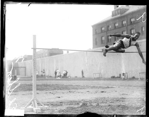 [African American track and field athlete Shaw leaping over a horizontal bar while performing a high jump at Stagg Field]