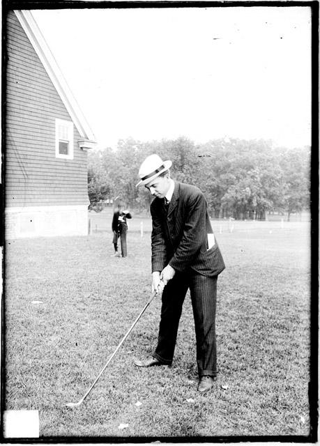 [Golfer, W. B. Egan standing outdoors and positioning a golf club, Midlothian Country Club]