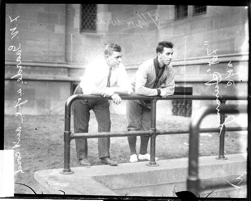 "[Assistant baseball coach F. W. Gaarde baseball player ""Fat"" Summy, both of the University of Chicago baseball team, leaning on a railing]"