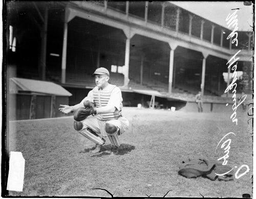 [Baseball catcher Heckinger, Cubs, crouching in front of grandstands on the field at West Side Grounds]