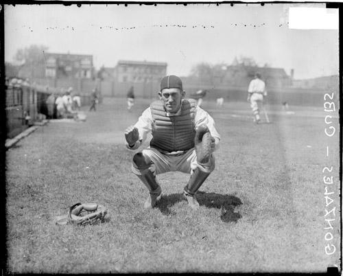 [Baseball catcher, Gonzales holding his hands in front of him, crouching on the field at Wrigley Field]