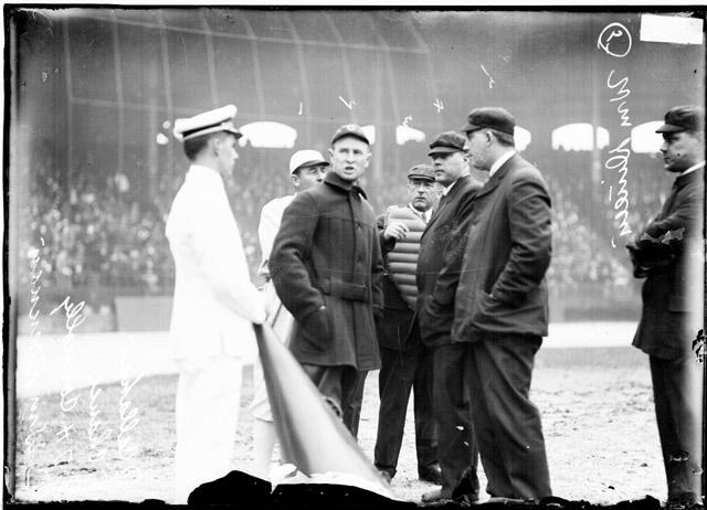 "[Baseball, City Series, players ""Nixey"" James J. Callahan, White Sox, and Frank Chance, Chicago Cubs, and umpires T. H. Connolly, C. L. Owens, William Dineen and William Brennan face a man in uniform on the field of Comiskey Park]"