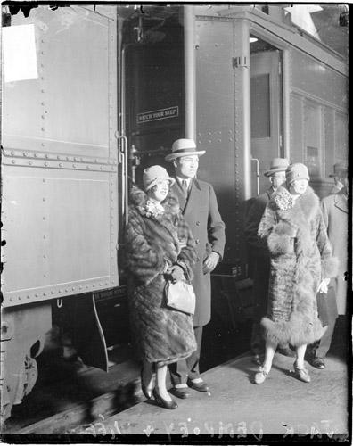 [Boxer, Jack Dempsey and his wife, Estelle Taylor Dempsey, in front of a passenger train car in a railroad station]