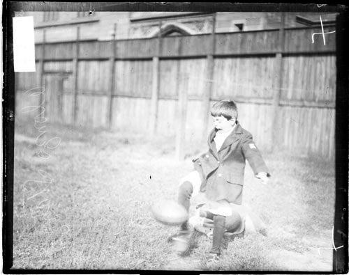 [Alonzo Stagg, Jr., young son of University of Chicago football coach Alonzo Stagg, Sr., looking down and kicking a football]