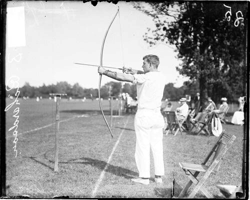 [Archer H. B. Richardson holding a bow and arrow and pulling back the bow string]