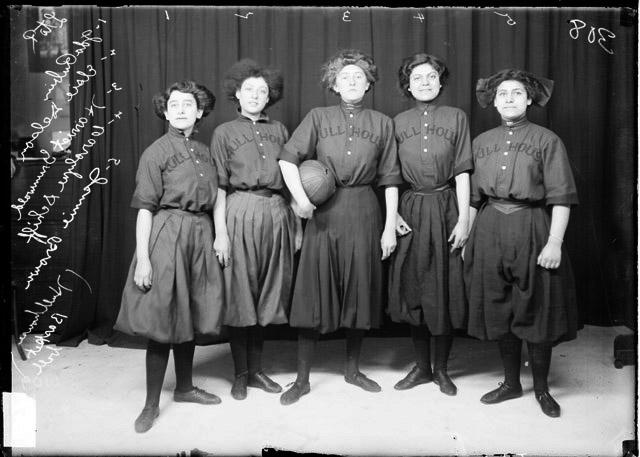 [Hull House girls' basketball players Ida Rubin, Elsie Delson, Harriet Grunwald Carolyn Schiff, and Jennie Brown, standing by a backdrop]