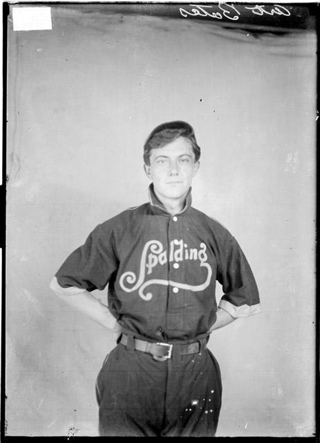 [Spalding baseball player Art Bates, standing in uniform in front of a light-colored backdrop in a room]