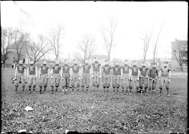 [Football team, Englewood High School, standing shoulder to shoulder on a field, light exposure]