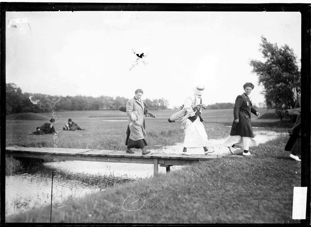 [Golfer, Margaret Curtis, and two unidentified golfers crossing a bridge carrying their golf clubs at the Midlothian Country Club]