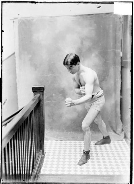 [Pugilist, Benny Yanger, facing his right, standing in a boxing stance in a stairwell hallway]