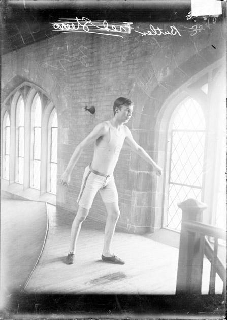 [Athlete, Butler, standing in relay position by the indoor track, Bartlett Gymnasium]