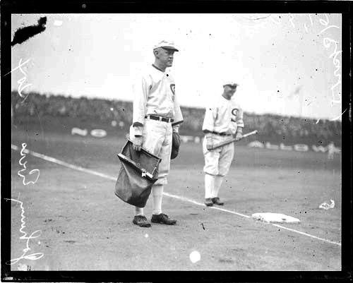 [Baseball coach/manager, White Sox, Johnny Evers standing in foul territory near third base holding bag]