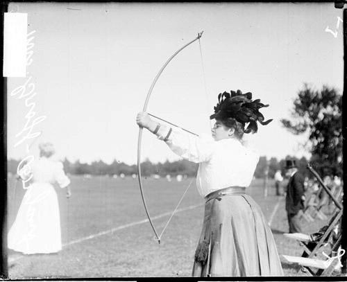 [Archer Mrs. Groff Bryant holding a bow and arrow and pulling back the bow string]