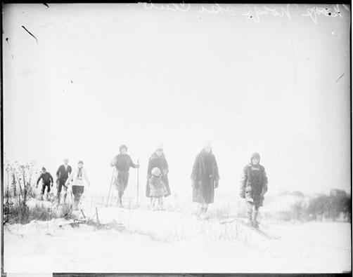 [Group of unidentified adults and children skiing over snow-covered ground at the Norge Ski, light exposure]