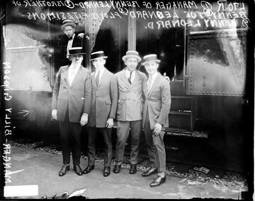 [Boxer, Benny Leonard standing with manager Gibson, brother Leonard, and promoter Fitzsimmons in front of a passenger train car]