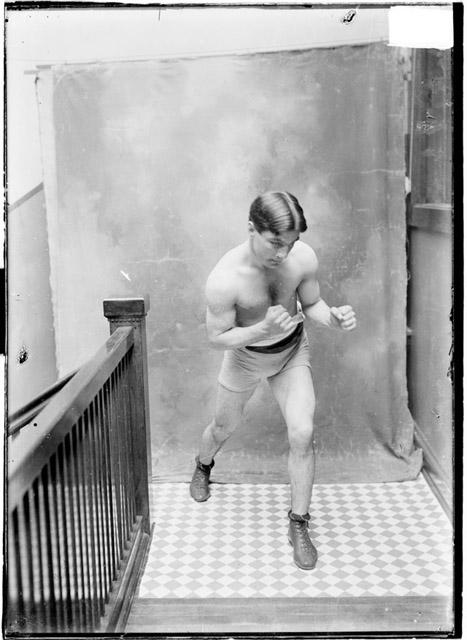 [Pugilist, Benny Yanger, turned to his left, chin tucked, standing in boxing stance in stairwell hallway]