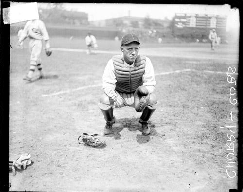 [Baseball catcher Jack Churry crouching on the field at Wrigley Field]