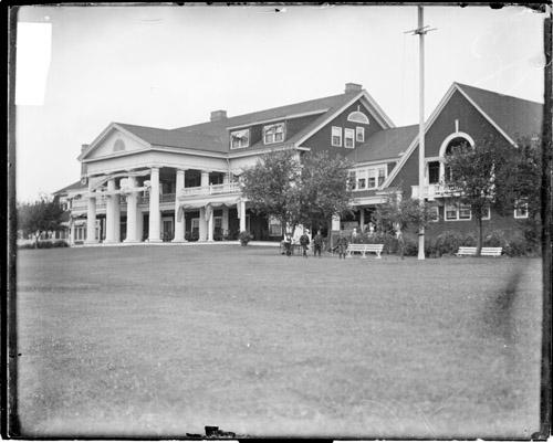 [Clubhouse of the Midlothian Golf Club in Midlothian, Illinois, viewed at an angle from a grass field in front of the building]