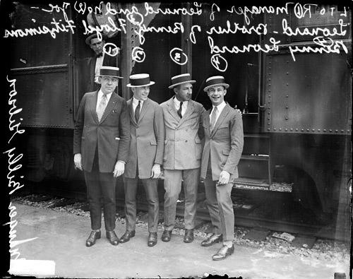 [Boxer, Benny Leonard standing with manager Gibson, brother Leonard, and promoter Fitzsimmons in front of a passenger train car at the La Salle Street station]